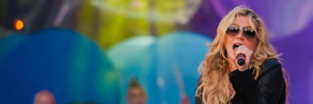 Kesha sings in an all-black outfit in front of a colorful backdrop