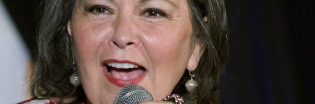 Roseanne Barr in a striped shirt speaks into a microphone