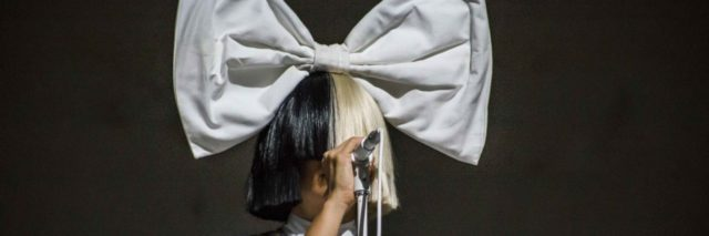 Sia singing onstage with a giant bow on her head