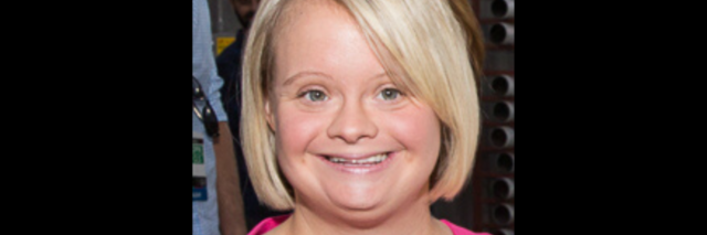 Lauren Potter, in a pink dress, smiles at the camera