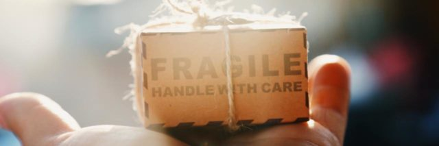 "hand holding a tiny brown paper package that says ""fragile open with care"""