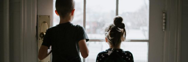 photo of two children from behind looking outside through glass door during coronavirus quarantine