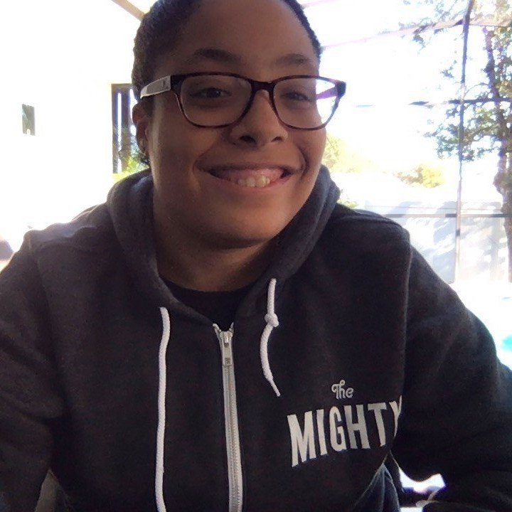 A woman smiling wearing a sweatshirt for The Mighty.