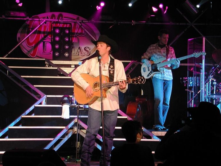 Clay Walker performs onstage with a guitar