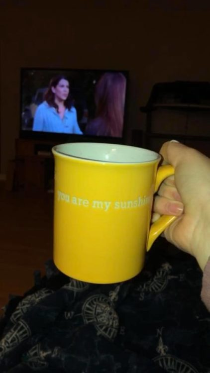 A person holds a mug in front of their television
