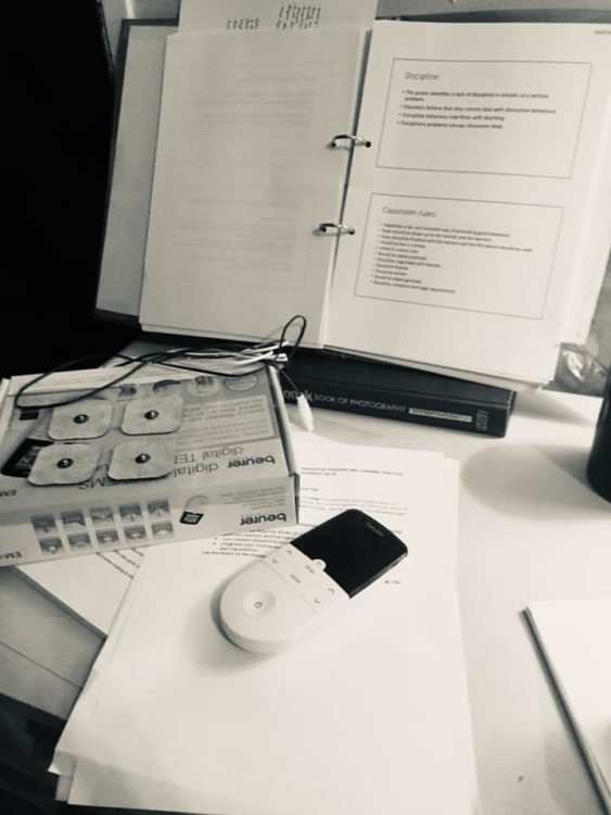 On a desk, there is a TENS unit and exam materials