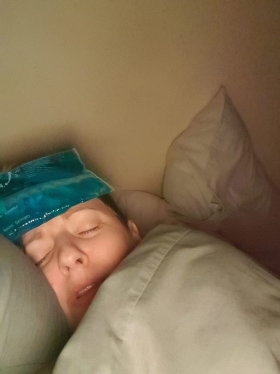 A woman lies down with her eyes closed with an ice pack on her head