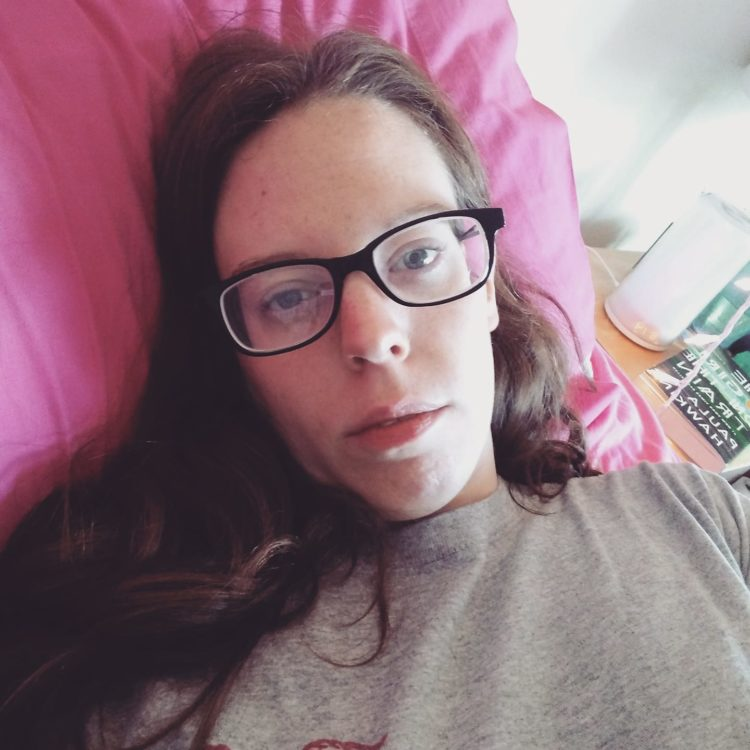 A woman with brown hair and glasses lies down on a bed.
