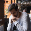 Sad guy sitting alone separately from friends in cafe.