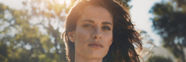 close up of a woman's face, standing in a field with trees, and the sun shining behind her