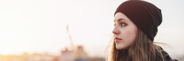 Young woman with hat at sunset