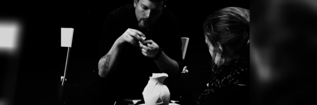 black and white photo of artist assembling a broken pitcher or jug