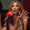 Wendy Williams speaks into a big red microphone