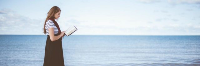 photo of woman standing on beach with bible