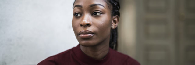 A black woman with braids looking serious