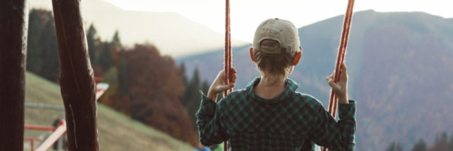 Boy on a swing looking at mountains.