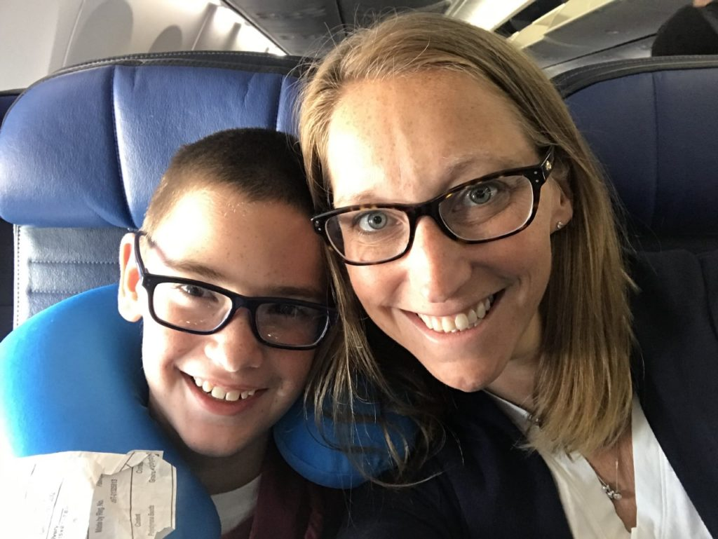 photo of contributor smiling and posing for the camera with her son while seated in airplane
