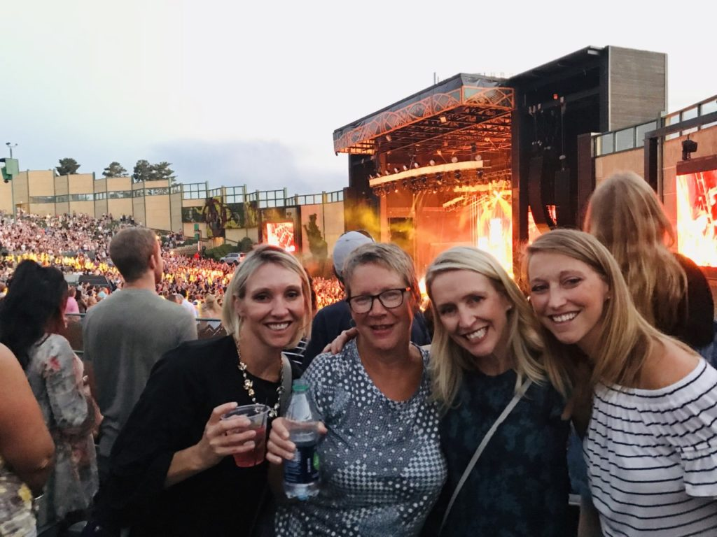photo of contributor and three other women at a concert, smiling