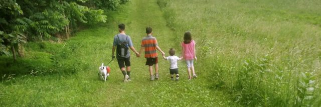 Heather's family walking in a field.