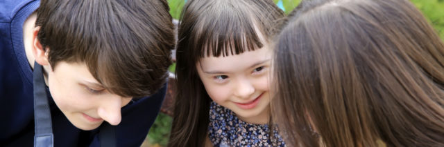 Teen with Down syndrome laughing with friends.