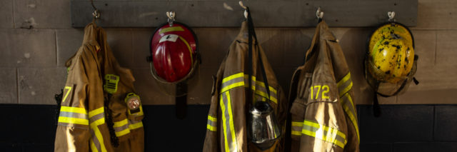 firefighter's clothing hanging in a firehouse