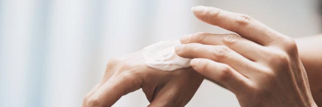 Woman applying moisturizing cream on hands.