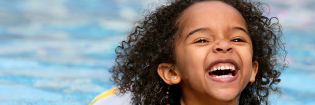 Happy young Black girl swimming in pool.