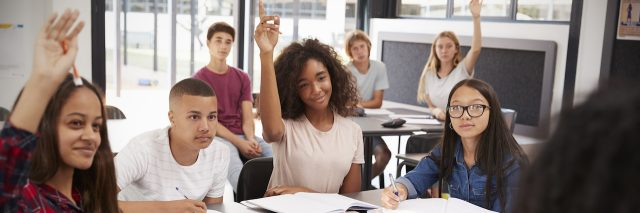 Diverse group of high school students raising hands in class