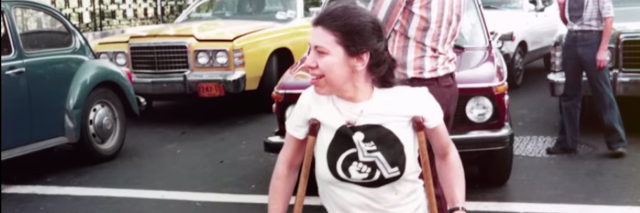 Woman wearing a white shirt with a wheelchair on it using crutches