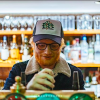 Ed Sheeran wearing a ball cap standing at the counter of a bar