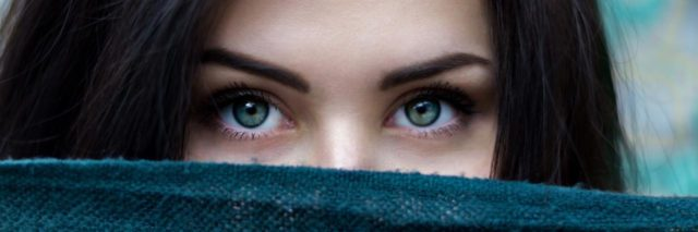 A woman looking from behind a blanket, all you can see are her eyes up