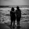 Two friends on a beach looking out over the water