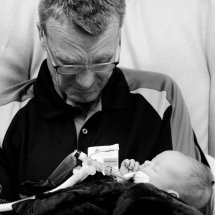 A grandfather holding a new baby