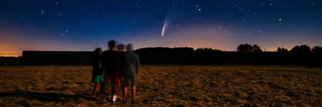 photo of group of people standing in a field looking at comet neowise in the distance just over the horizon