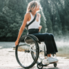 Woman in a manual wheelchair with forest in the background.