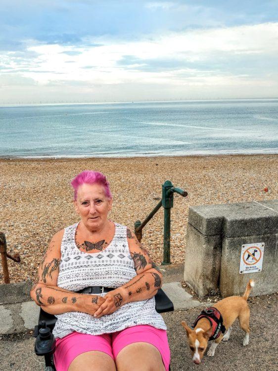 A woman with pink hair near a beach