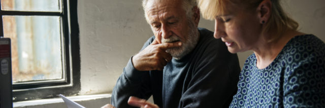 photo of older couple making a decision on something with a laptop