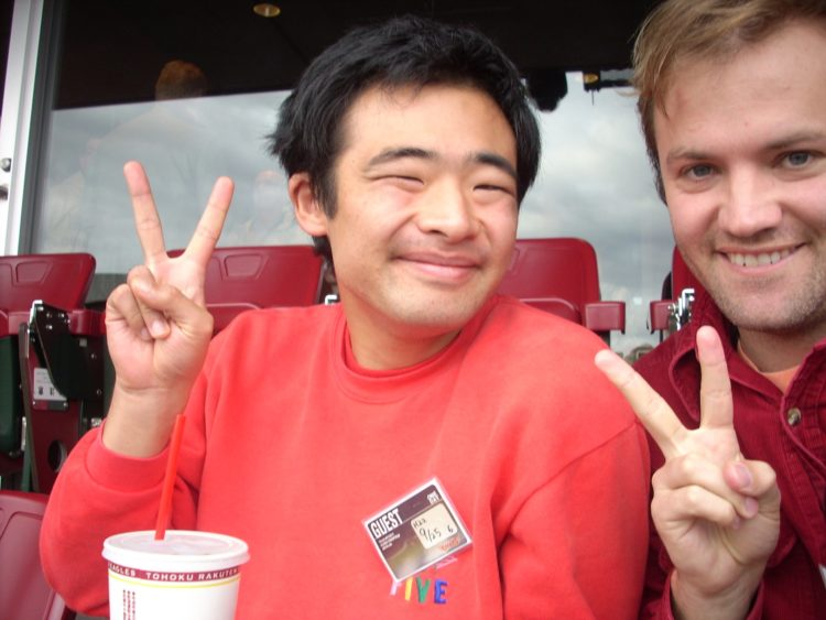 Contributor with his student, both making peace signs
