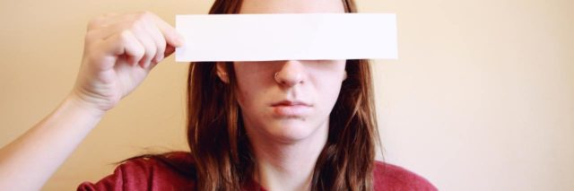 photo of young woman hiding her eyes with a rectangle of paper