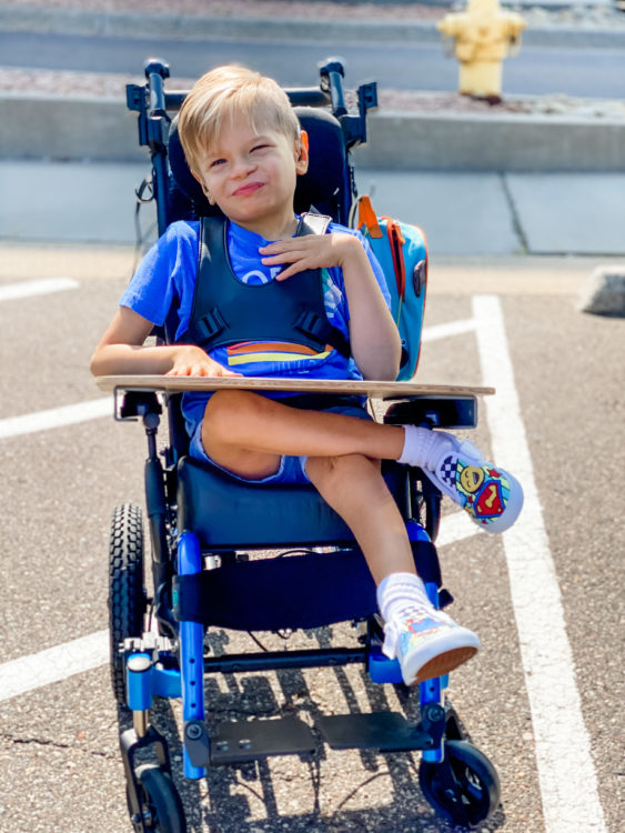 the author's son, sitting in his wheelchair with his leg crossed, smiling at the camera. he's outside in a parking lot.
