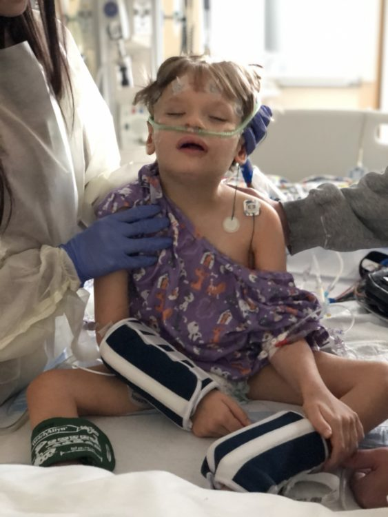 The author's child, sitting on a hospital bed with a blood pressure cuff, oxygen, and heart monitor nodes