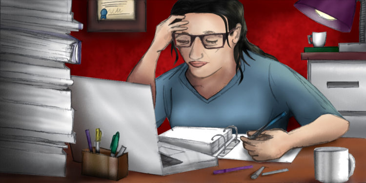 Stressed female therapist works on paperwork on her computer surrounded by piles of books