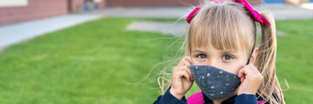 Girl wearing a mask and school backpack.