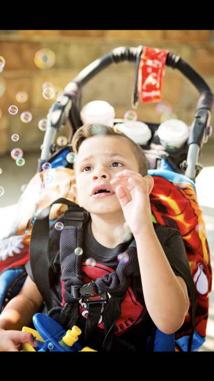 the author's child in a wheelchair/stroller, looking up at bubbles around him, trying to touch them