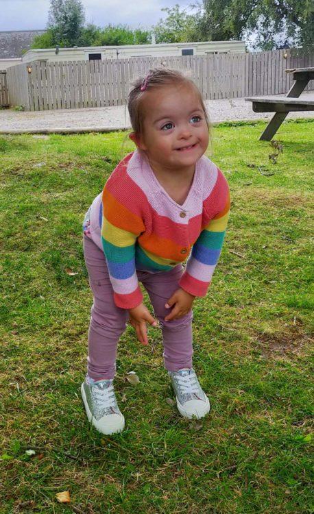 Rachel's daughter wearing a rainbow striped shirt.