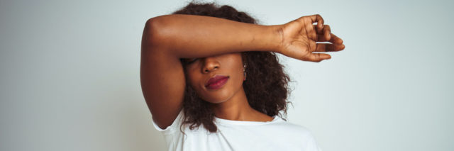 Young african american woman wearing t-shirt standing over isolated white background covering eyes with arm, looking serious and sad.