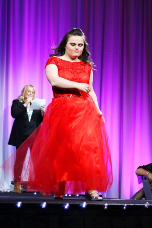 Rachel on stage in a red dress.