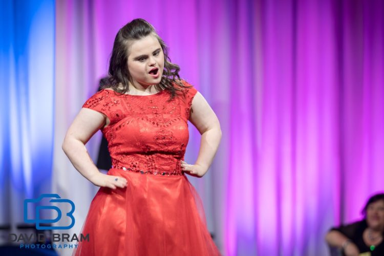 Rachel striking a pose on stage wearing a red dress.