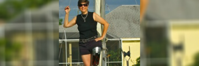 Deb standing on a boat. Her prosthetic leg is visible.