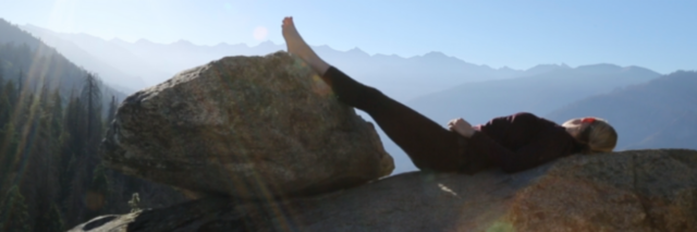 Woman looking out over mountain view with feet resting on a rock